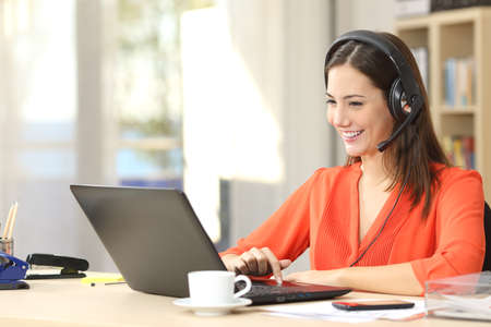 Beautiful freelancer female talking in a video conference on line with a headset with microphone and laptop in an office desktop or home desk