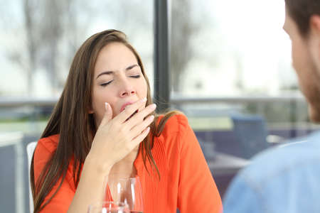 Woman bored or tired yawing in a bad date in a coffee shop with a window in the background