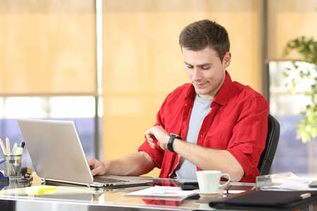 Businessman working and checking smart watch or clock sitting in a desktop at office