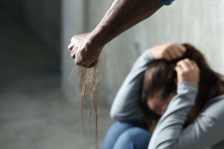 Domestic violence with a man hurting to a terrified woman pulling hair and holding it in the fist in a dark place