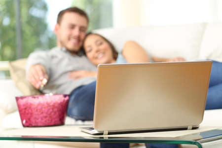 Happy couple watching tv on line in a laptop and eating popcorn lying on a comfortable sofa at home