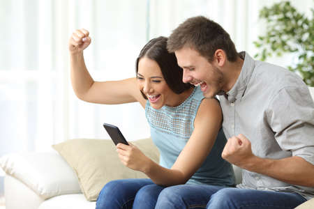 Excited couple watching media content together using a mobile phone sitting on a couch in the living room of a house