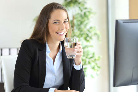 Businesswoman wearing suit  holding a water glass in a desk and looking at camera at office