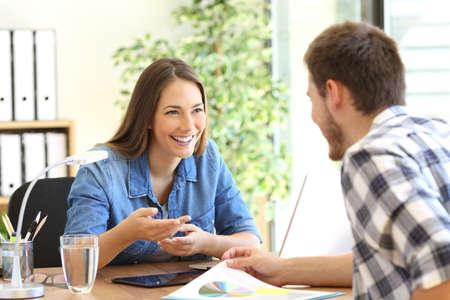 Happy entrepreneurs having a business conversation in a desktop at office