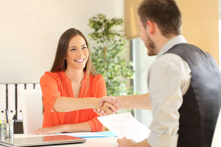 Happy employee and boss handshaking after a successful job interview at office