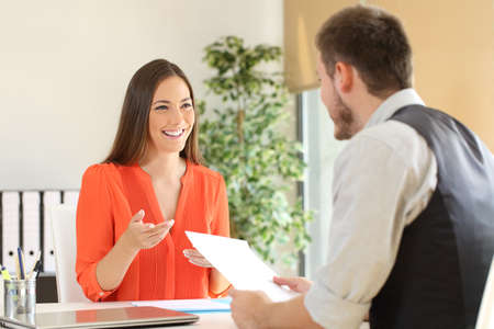 Confident woman and interviewer looking each other and talking during a job interview at office