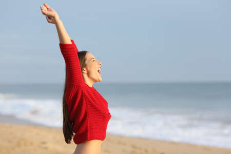 Side view of an excited woman wearing a red sweater screaming on the beach