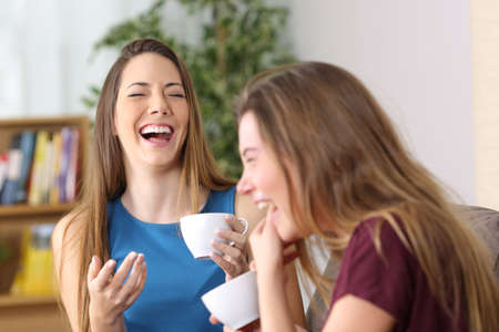 Portrait of two friends laughing loud together during a conversation sitting on a couch in the living room at home