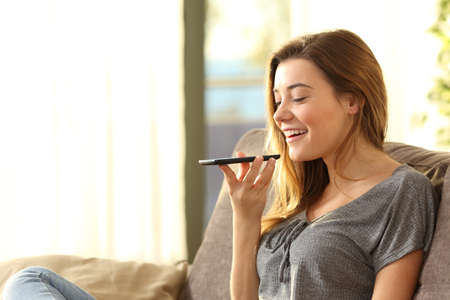 Girl using a smart phone voice recognition on line sitting on a sofa in the living room at home with a warm light and a window in the background