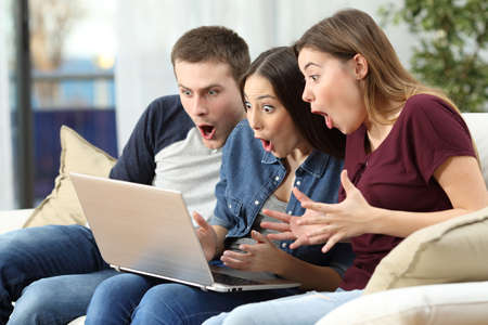 Three amazed friends watching media content on line in a computer sitting on a couch in the living room at home