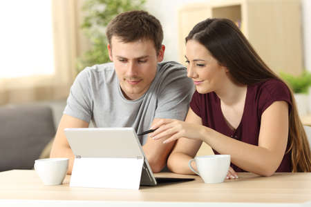 Couple searching on line content with a tablet pc sitting in a table in the living room at home with a window in the background