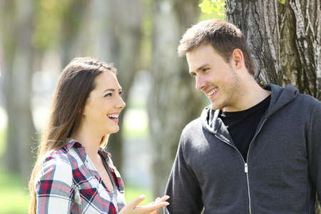 Two happy teen friends talking and looking each other in a park