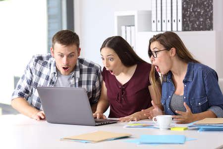 Photo pour Three amazed entrepreneurs receiving good news on line at office - image libre de droit