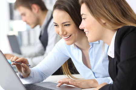 Two businesswomen working together on line with a laptop at office