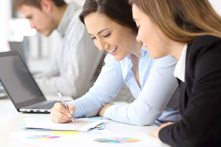 Close up of two happy businesswomen working together at office