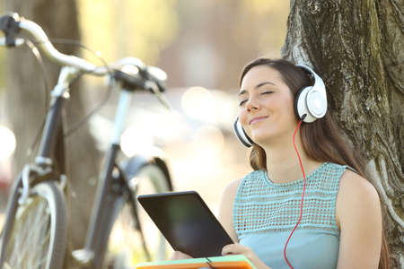 Single student wearing headphones listening to music on line with a tablet outdoors in a park