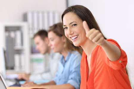 Portrait of a happy employee looking at you with thumbs up sitting in a desktop at office