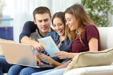 Three happy friends planning a travel on line and consulting a guide sitting on a sofa at home