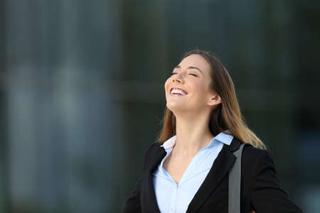 Single happy successful executive breathing deep fresh air on the street with an office building in the background