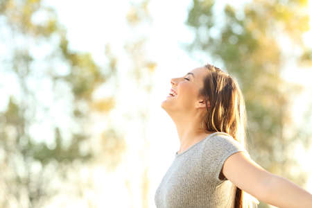 Photo pour Side view portrait of a woman breathing fresh air outdoors in summer with trees and sky in the background - image libre de droit