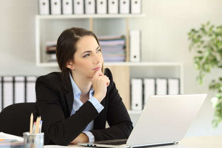 Pensive office worker wondering looking at side sitting in a desktop at workplace