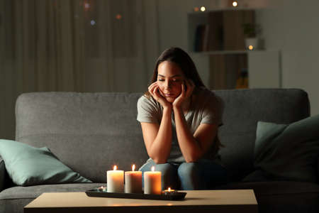 Distracted woman looking at candles light during blackout sitting on a couch in the living room at home