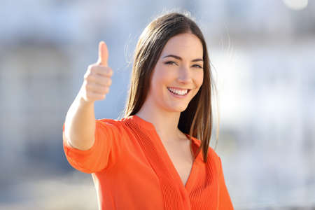 Happy woman in orange gesturing thumb up in a town outskirts a sunny day
