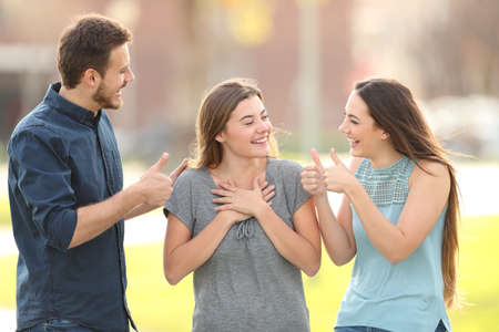 Two friends congratulating a happy girl standing in the street