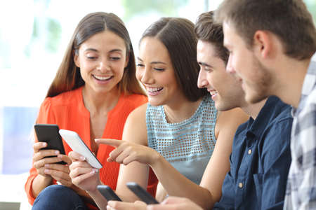 Photo pour Happy group of friends checking smart phones sitting on a couch in the living room at home - image libre de droit