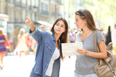Photo for Lost tourist asking for help from a pedestrian in the street - Royalty Free Image