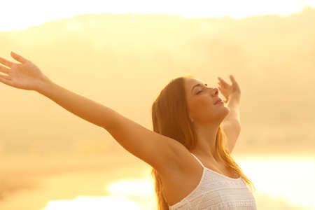 Photo for Relaxed woman stretching arms breathing deep fresh air at sunset on the beach - Royalty Free Image