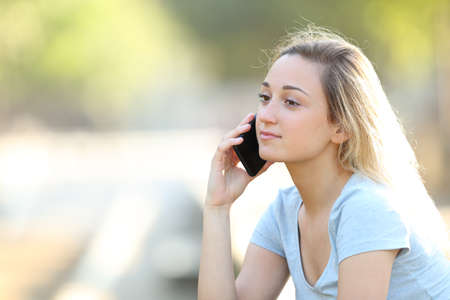 Photo for Serious teenage girl talking on smart phone sitting in a park - Royalty Free Image