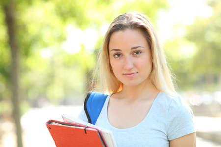 Foto de Serious teenage student standing looking at camera in a park - Imagen libre de derechos