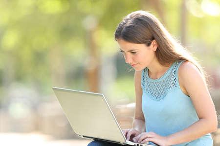 Foto de Serious woman sitting in a park using a laptop to search online content - Imagen libre de derechos