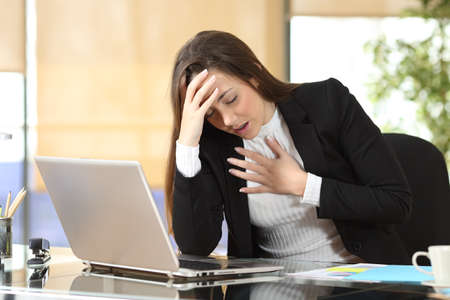 Worried businesswoman suffering an anxiety attack due to stressful life at office
