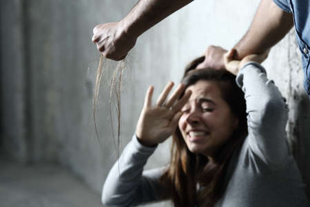 Photo for Scared abuse victim being attacked by a mad man in a dark place - Royalty Free Image
