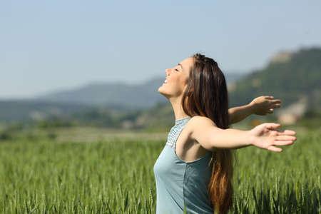Foto de Side view portrait of a happy woman breathing deeply fresh air in a green field - Imagen libre de derechos