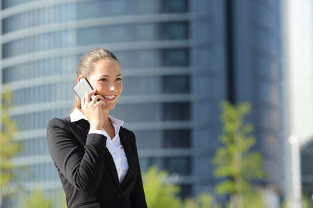 Photo pour Happy businesswoman talking on phone and walking in the street - image libre de droit