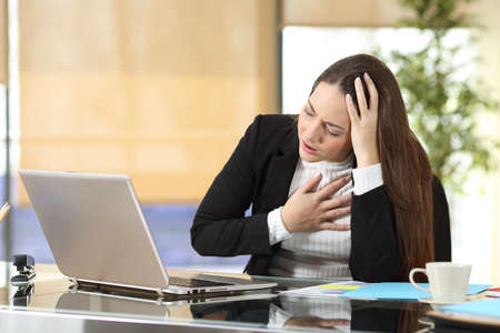 Businesswoman with stressful work suffering an anxiety attack at office