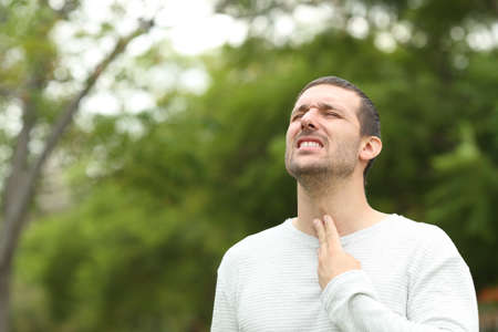 Photo for Man suffering throat ache complaining standing alone in a park - Royalty Free Image