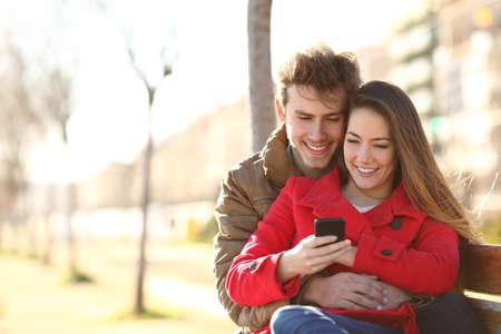 Foto de Happy couple browsing content on smart phone sitting on a bench in the street in winter - Imagen libre de derechos