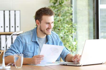 Photo pour Casual happy entrepreneur working using laptop holding document comparing data at office - image libre de droit