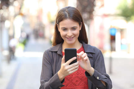 Photo for Front view portrait of a happy teen checking mobile phone content walking in the street - Royalty Free Image