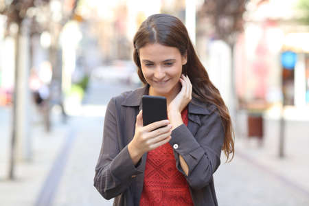 Photo for Front view portrait of a candid teen checking smart phone text walking in the street - Royalty Free Image