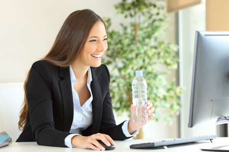 Photo for Happy executive working holding a bottle of water  using computer at office - Royalty Free Image