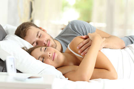 Photo for Relaxed couple resting sleeping lying on a bed at home or apartment - Royalty Free Image