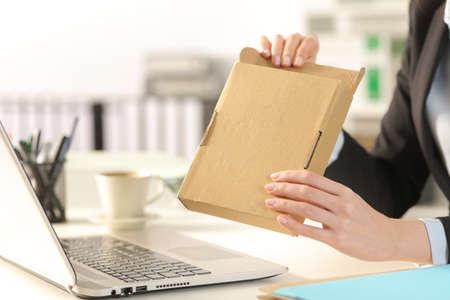 Foto de Close up of executive woman hands opening delivery package on a desk at the office - Imagen libre de derechos