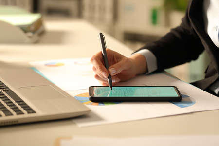 Foto de Close up of executive woman hands filling out form with stylus on smart phone at night in the office - Imagen libre de derechos