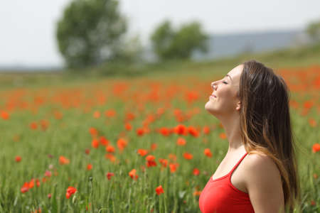 Photo for Profile of a satisfied woman breathing fresh air on a green poppy field in spring - Royalty Free Image