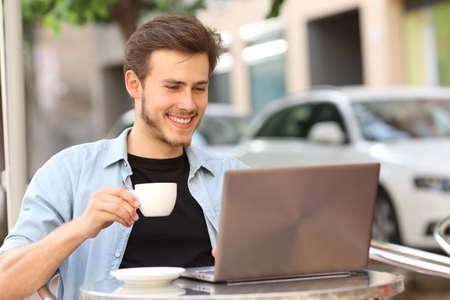 Foto de Happy man reading on laptop holding cup sitting on a coffee shop terrace - Imagen libre de derechos